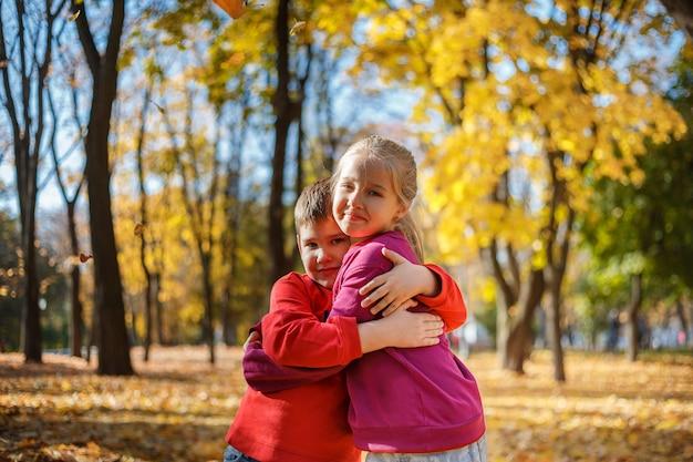 Petit garçon et fille dans un parc en automne. garçon embrassant une fille Photo Premium