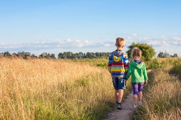 Petit garçon et fille, marcher ensemble, tenant mains Photo Premium