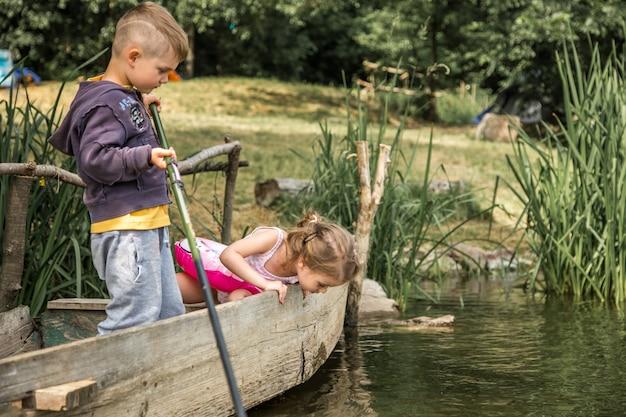 Petit Garçon Fille Pêche Dans Un Bateau Photo gratuit