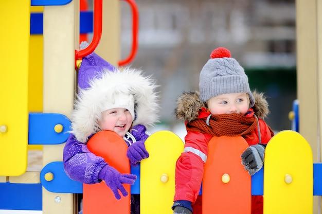 Petit Garçon Et Fille En Vêtements D'hiver S'amuser Dans L'aire De Jeux En Plein Air Photo Premium