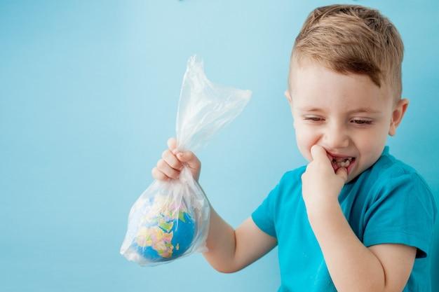 Petit Garçon Avec Un Globe Dans Un Emballage Sur Fond Bleu Photo Premium
