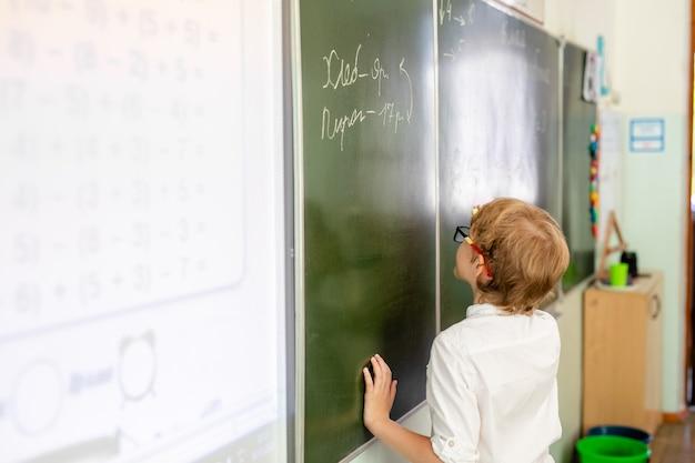 Petit garçon avec de grandes lunettes noires et une chemise blanche se tenant près du tableau de l'école avec un morceau de craie faisant face intelligente Photo Premium