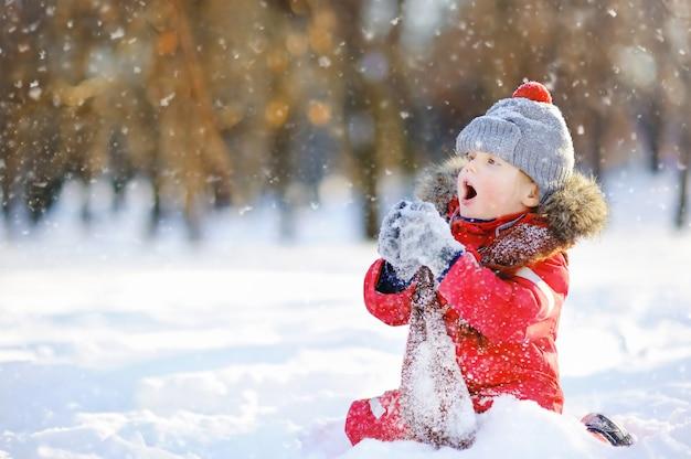 Petit garçon en habits d'hiver rouge s'amuser avec la neige Photo Premium