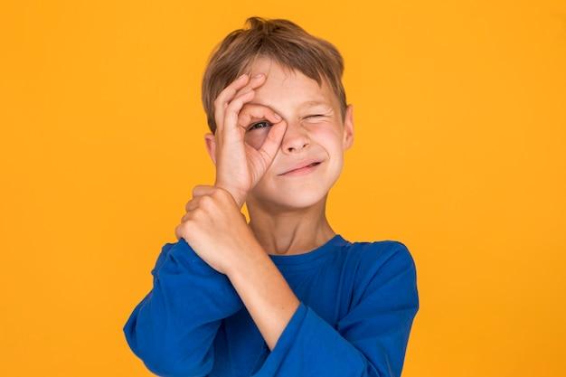 Petit garçon imitant un monocle Photo gratuit