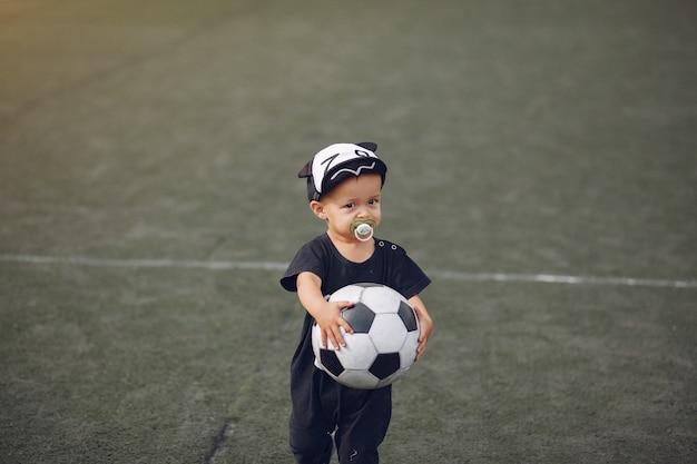 Petit Garçon Jouant Au Football Dans Un Terrain De Sport Photo gratuit