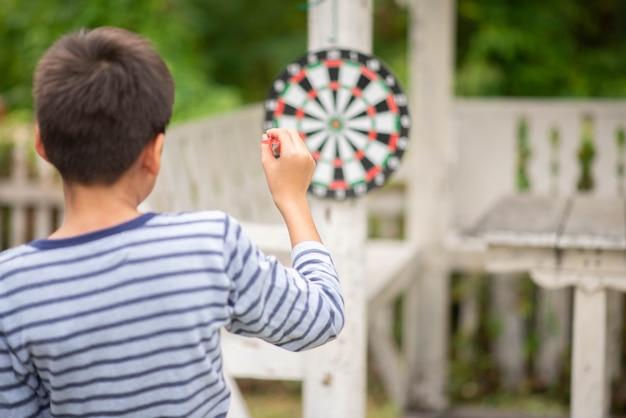 Petit garçon jouant au jeu de fléchettes en famille Photo Premium