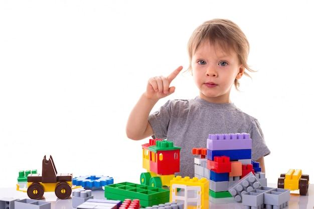 Petit garçon jouant avec des blocs de jouet, pointant son doigt vers le haut, visage concentré isolé Photo Premium