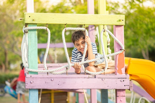 Petit garçon jouant dans l'aire de jeux en plein air Photo Premium