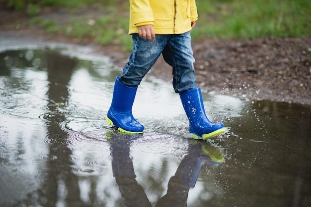 Petit garçon jouant dans une flaque d'eau Photo Premium