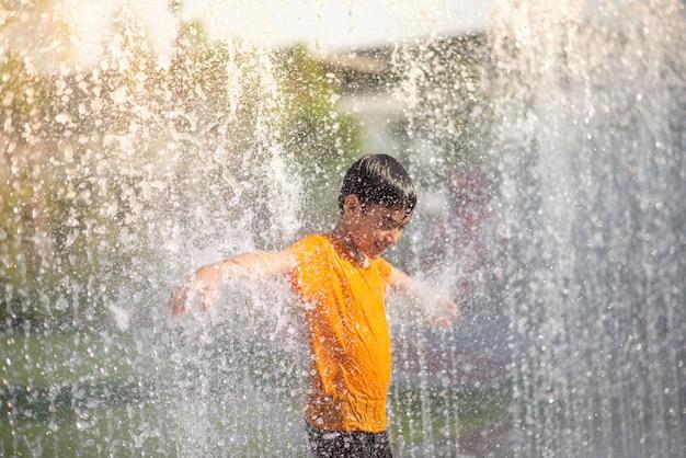 Petit Garçon Jouant Des Gouttes D'eau Fontaine Sous Le Tissu Et Un Parapluie Photo Premium