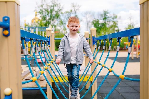 Petit garçon jouant sur le terrain de jeu. Photo Premium