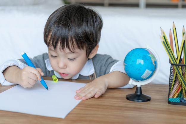 Petit garçon joyeux avec crayon de couleur orange, dessin sur papier blanc Photo gratuit