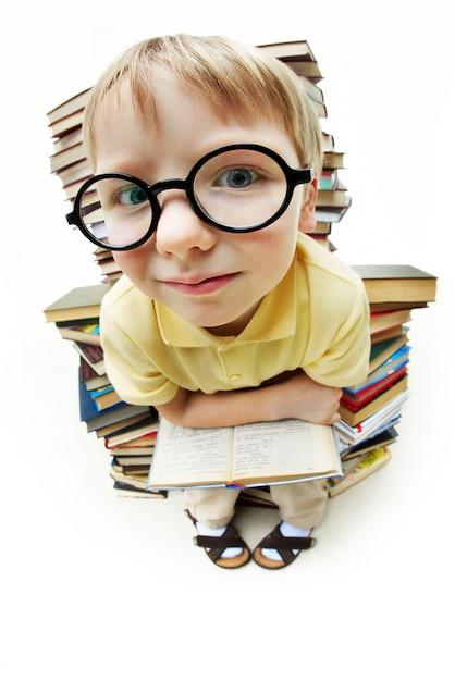 Petit garçon avec des lunettes entouré de livres Photo gratuit