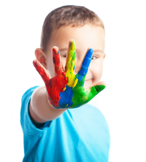 Petit garçon avec une main pleine de peinture couvrant son visage Photo gratuit