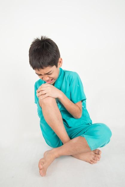 Un petit garçon a mal aux jambes à cause de douleurs musculaires au genou Photo Premium