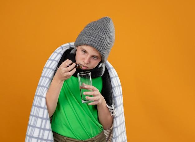 Petit Garçon Malade Portant Un Chapeau Chaud Et Une écharpe Enveloppée Dans Une Couverture Dégoulinant De Gouttes De Flacon De Médicament Dans Un Verre Debout Sur Un Mur Orange Photo gratuit