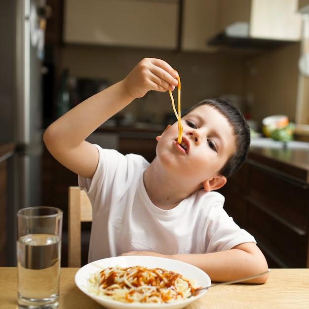 Petit garçon mange des pâtes avec les mains Photo gratuit