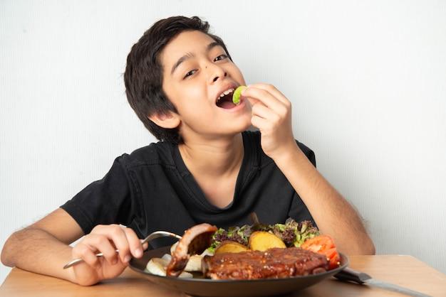 Petit Garçon, Manger, Porc Côte, Gril, à, Figure Heureuse Photo Premium