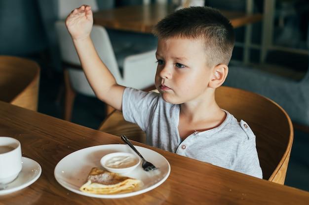 Petit garçon mignon prenant son petit déjeuner au café. Photo Premium