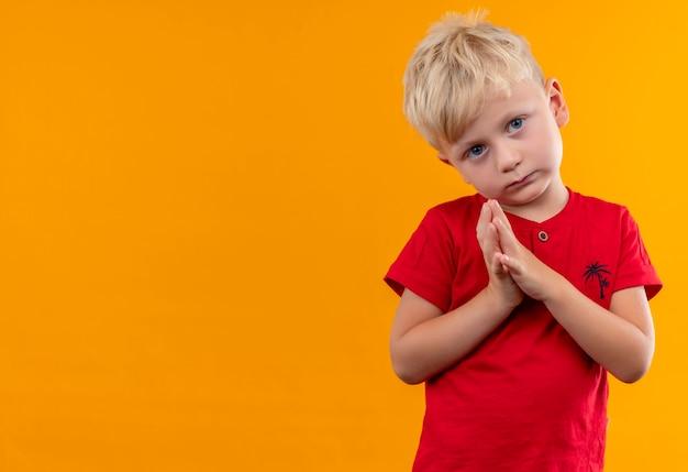 Un Petit Garçon Mignon Et Sérieux Aux Cheveux Blonds Et Aux Yeux Bleus Portant Un T-shirt Rouge à La Recherche Tout En Maintenant La Main Sur Un Mur Jaune Photo gratuit