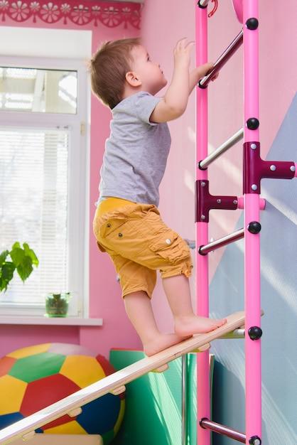 Le petit garçon monte une plaque de bois dans la salle de sport Photo Premium