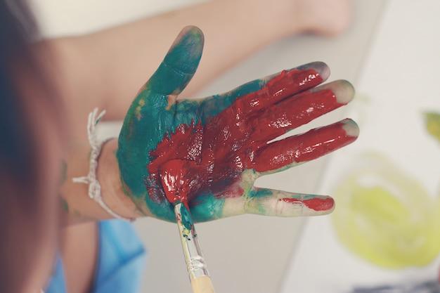 Petit garçon montrant des mains peintes en couleurs Photo Premium