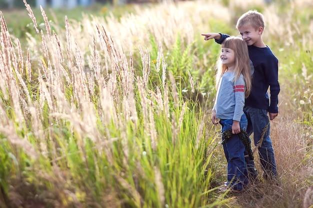 Petit garçon et petite fille debout main dans la main à la recherche sur horizont. vue arrière. Photo Premium