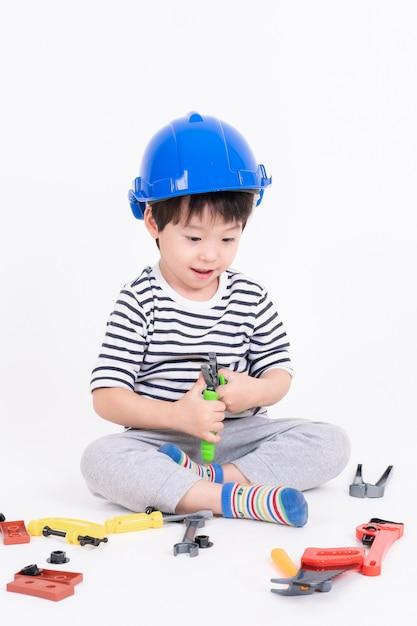 Petit Garçon Portant Casque Bleu Assis Et Jouant Avec Des Engins De Chantier Jouet Sur Blanc Photo gratuit