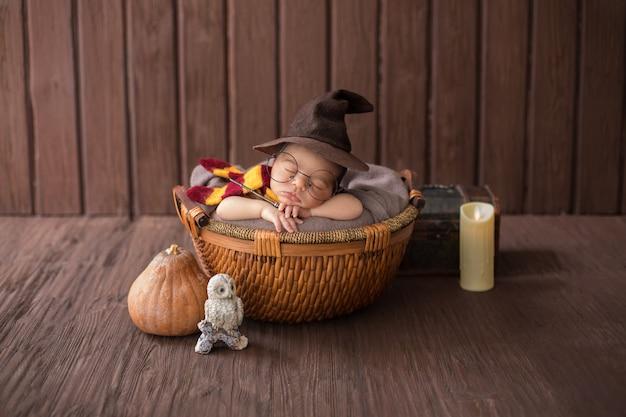Petit garçon portant à l'intérieur d'un petit panier avec un costume de sorcier drôle Photo gratuit
