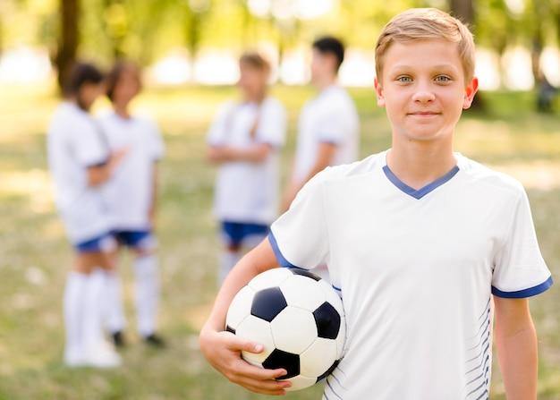 Petit Garçon Posant Avec Un Football à L'extérieur Photo gratuit