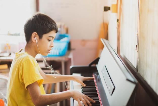 Petit Garçon Pratiquant Le Piano Tablette Numérique En Ligne à La Maison Photo Premium