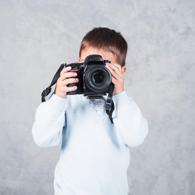 Petit garçon prenant une photo avec l'appareil photo Photo gratuit