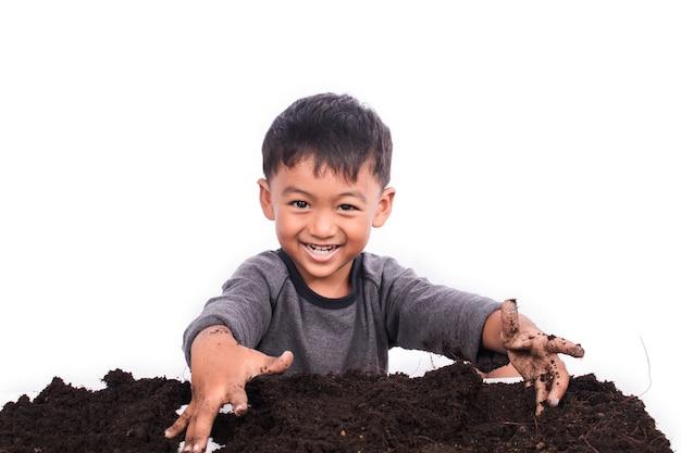 Petit garçon prépare le sol pour la plantation Photo Premium