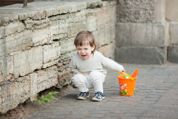 Petit garçon qui pleure debout dans la rue. Photo Premium