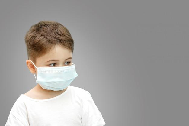 Petit Garçon De Race Blanche Dans Un Masque Médical Sur Fond Isolé Photo Premium