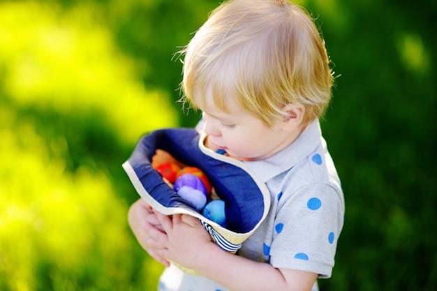 Petit garçon à la recherche de l'oeuf dans le jardin de printemps le jour de pâques. mignon petit enfant avec des oeufs de pâques traditionnels célébrant la fête Photo Premium