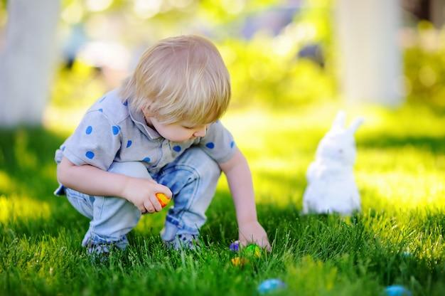 Petit garçon à la recherche de l'oeuf de pâques dans le jardin de printemps le jour de pâques. adorable petit enfant avec un lapin traditionnel Photo Premium