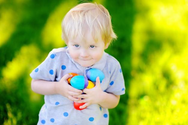 Petit garçon à la recherche de l'oeuf de pâques dans le jardin de printemps le jour de pâques. mignon petit enfant fête célébrant Photo Premium