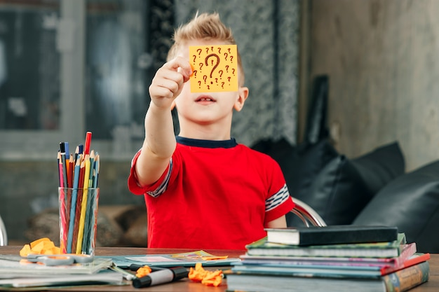 Le petit garçon réfléchissait, collant un autocollant sur son front. résout le problème. Photo Premium