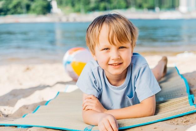 Petit garçon en regardant la caméra et souriant sur la plage Photo gratuit