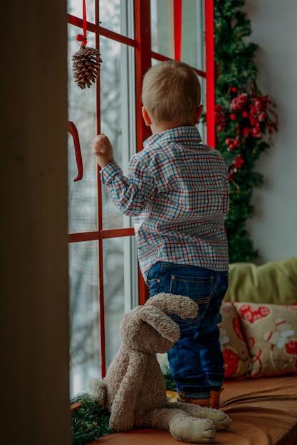 Petit garçon regardant par la fenêtre à noël Photo Premium