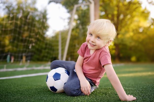 Petit garçon s'amusant à jouer à un match de foot / football le jour de l'été. jeu de plein air actif / sport pour enfants. Photo Premium