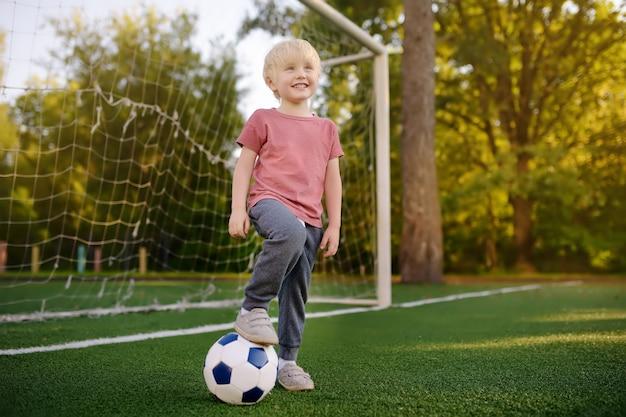 Petit Garçon S'amusant à Jouer à Un Match De Foot / Football Le Jour De L'été. Photo Premium