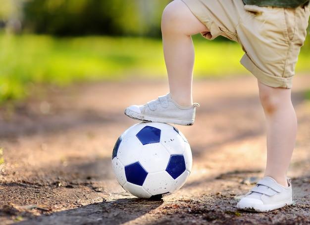 Petit garçon s'amusant à jouer à un match de foot / football le jour d'été Photo Premium