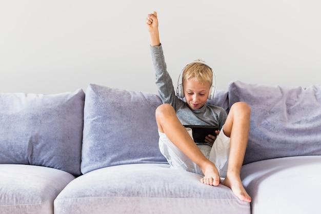 Petit garçon s'amusant avec tablette et écouteurs Photo gratuit