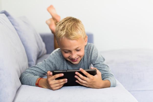 Petit garçon s'amusant avec tablette Photo gratuit