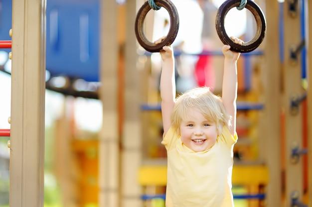 Petit garçon s'amuser sur une aire de jeux extérieure. sports d'été actifs pour les enfants Photo Premium