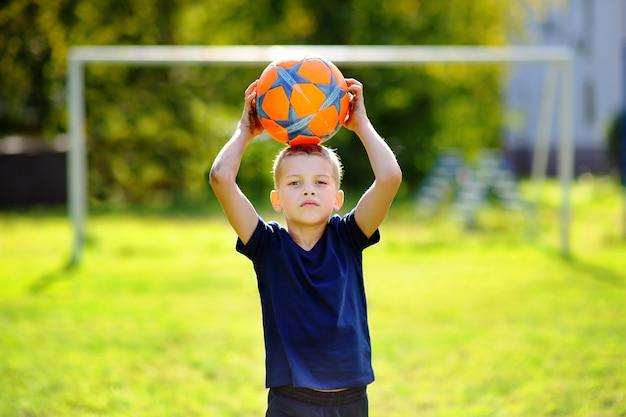 Petit garçon s'amuser jouer à un match de football sur une journée d'été ensoleillée Photo Premium