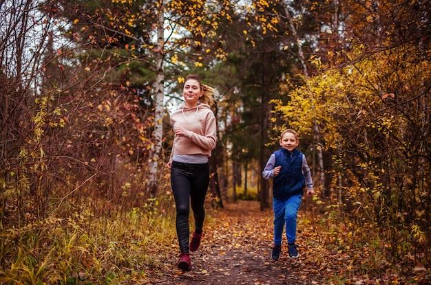 Petit garçon et sa soeur courir dans la forêt d'automne Photo Premium