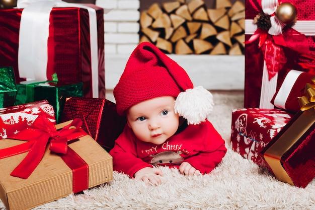 Petit Garçon De Santa Couché Sur Le Sol Dans Une Maison Décorée Avec Des Cadeaux De Noël Photo Premium